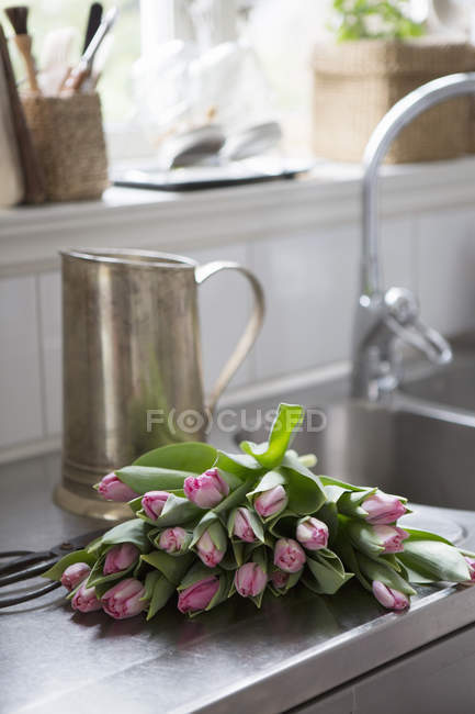 Tulips and metal jug on kitchen counter — Stock Photo