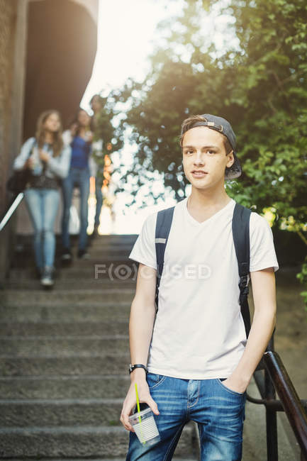 Portrait of confident teenager holding disposable glass while standing on steps with people in background — Stock Photo