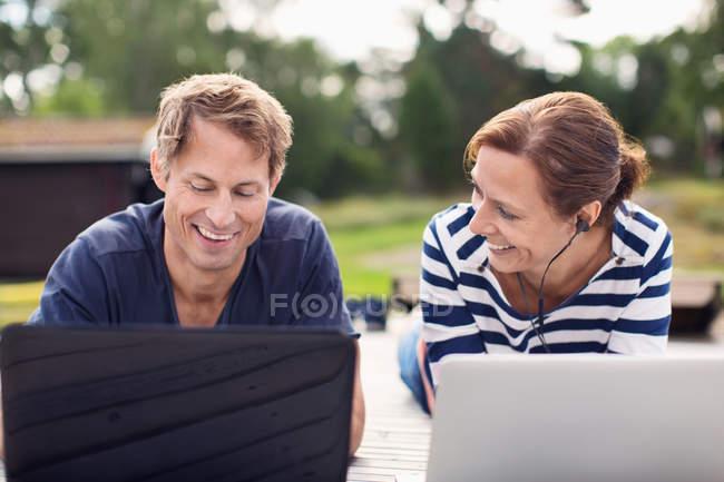 Sonriendo pareja madura usando computadoras portátiles mientras está acostado en el muelle - foto de stock