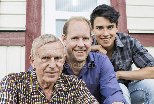 Portrait of multi-generation family sitting together outside house — Stock Photo