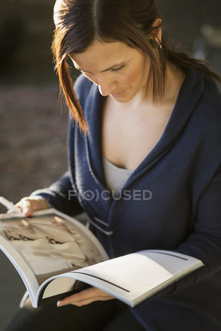 Businesswoman reading magazine in office — Stock Photo