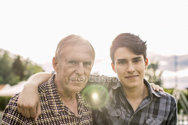 Portrait of confident grandfather and grandson with arms around against sky — Stock Photo