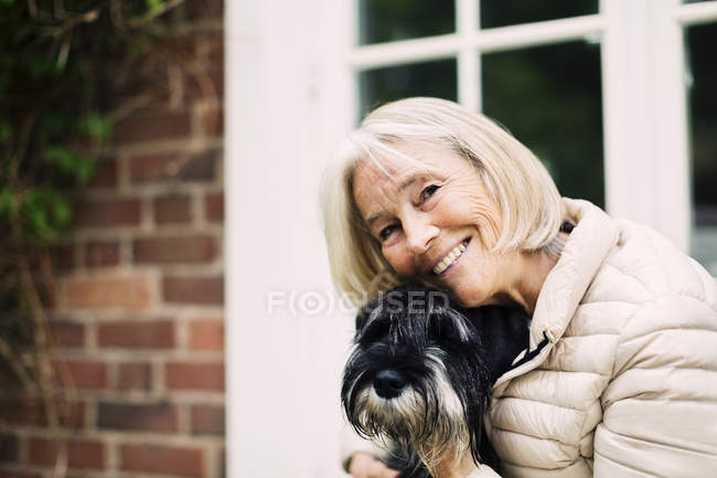 Portrait of happy senior woman with dog outside house — Stock Photo
