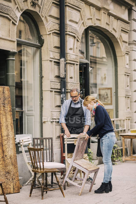 Retailer assisting customer in choosing chair outside antique shop — Stock Photo