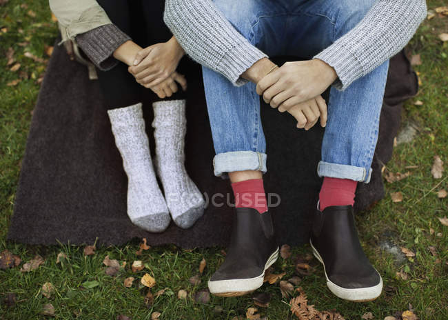 Low section of couple sitting on blanket while camping — Stock Photo