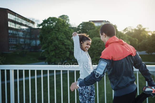 Happy friends stretching while standing by railing — Stock Photo