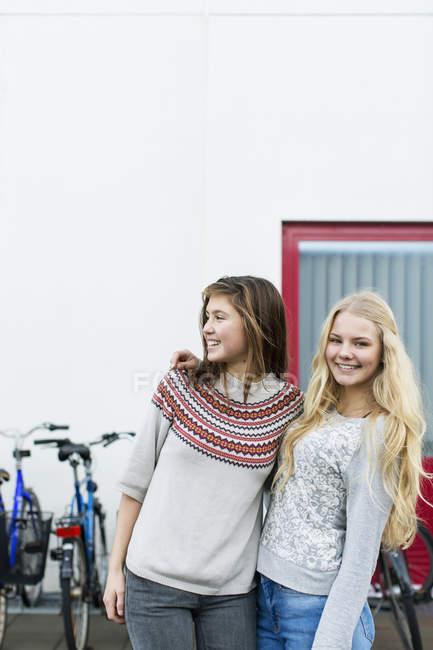 Portrait of happy teenage girl with friend on high school campus — Fotografia de Stock