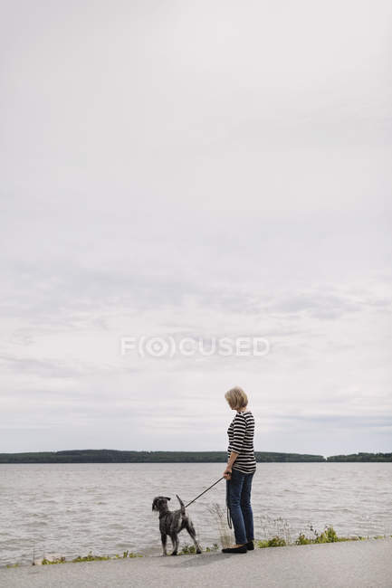 Side view of senior woman standing with dog at lakeshore against sky — Stock Photo