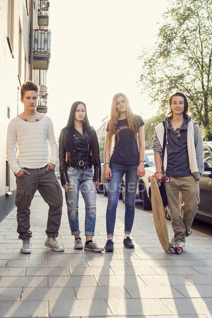 Ritratto completo di studenti delle scuole superiori sicuri in piedi sul marciapiede — Foto stock