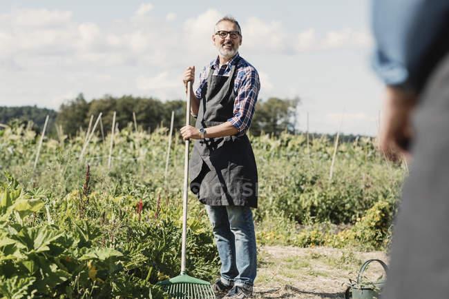 Exploitation agricole mature fourchette de jardinage et debout avec un collègue à la ferme — Photo de stock