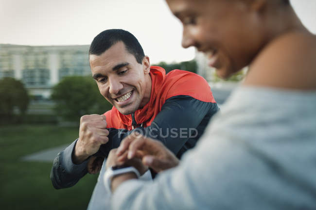 Man celebrating victory while woman checking time on smart watch — Stock Photo