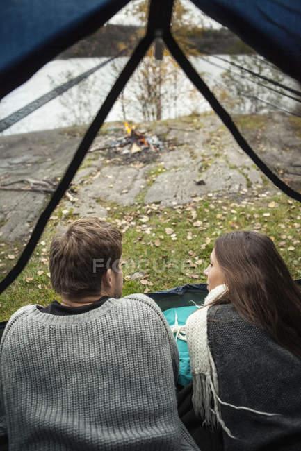 Vista posteriore di giovani coppie che si trovano in tenda a lakeshore — Foto stock