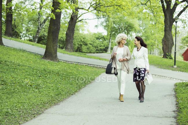 Full length of senior women walking on garden path — Stock Photo