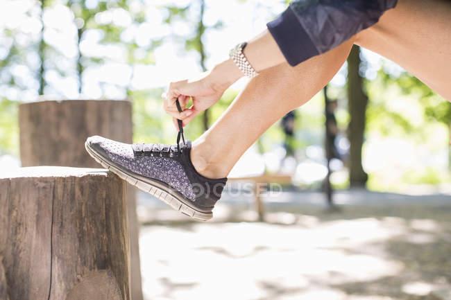 Faible section de femme fit attacher le lacet avant de faire du jogging dans le parc — Photo de stock