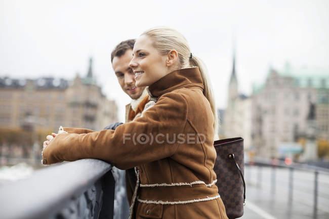 Side view of couple standing on bridge — Stock Photo