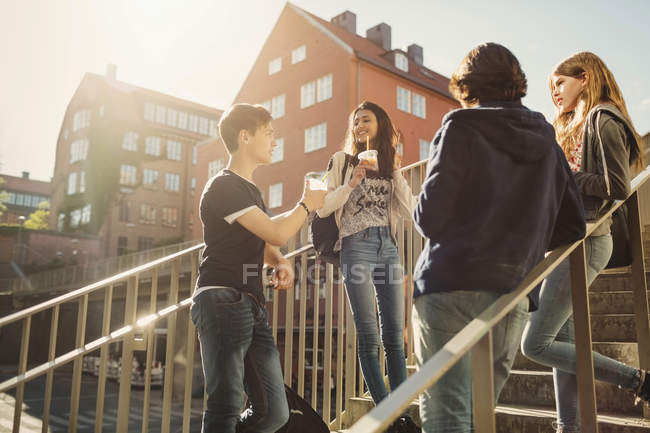 Teenagers talking while having drinks on steps in city — Stock Photo