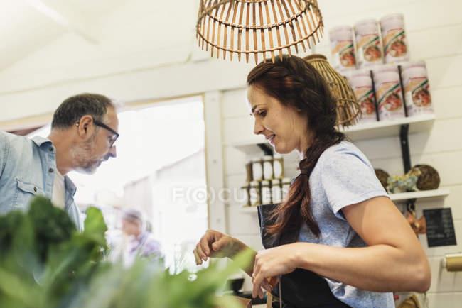 Vista a basso angolo di impiegato donna con cliente maturo al negozio di alimentari — Foto stock