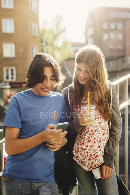 Happy teenagers using smart phone on steps in city — Stock Photo