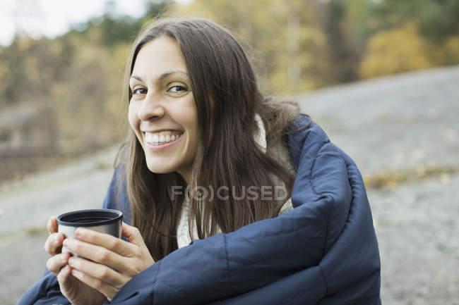 Retrato de mulher feliz embrulhado no cobertor, segurando a xícara de café ao acampar — Fotografia de Stock