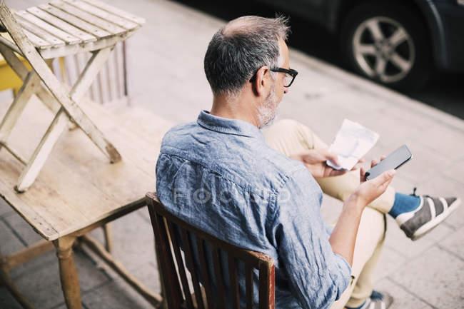 Vista ad alto angolo dell'uomo che utilizza il telefono cellulare mentre è seduto sulla sedia — Foto stock