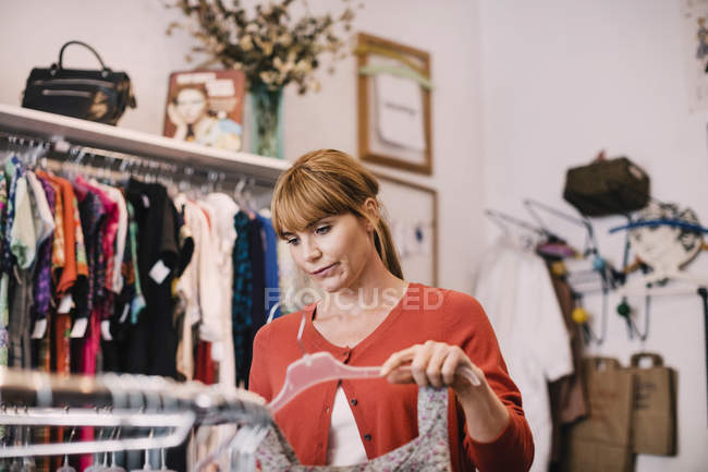 Owner arranging dress on clothes rack at thrift store — Stock Photo