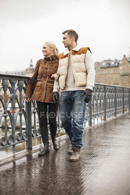 Full length of young couple walking on bridge — Stock Photo