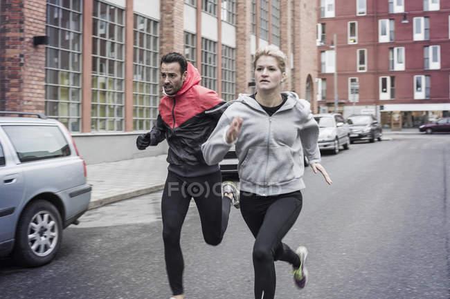 Спортивная пара бегает по улице — стоковое фото