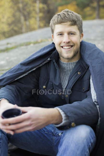 Porträt eines glücklichen Mannes in Decke gehüllt mit Kaffeetasse beim Zelten — Stockfoto