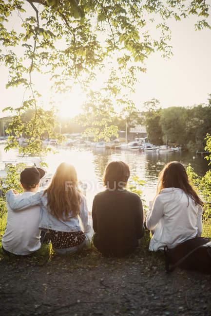 Vista posteriore di adolescenti maschii e femminili che si siede a lakeshore — Foto stock