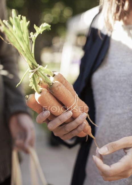 Midsection of woman holding carrot at street market — Stock Photo