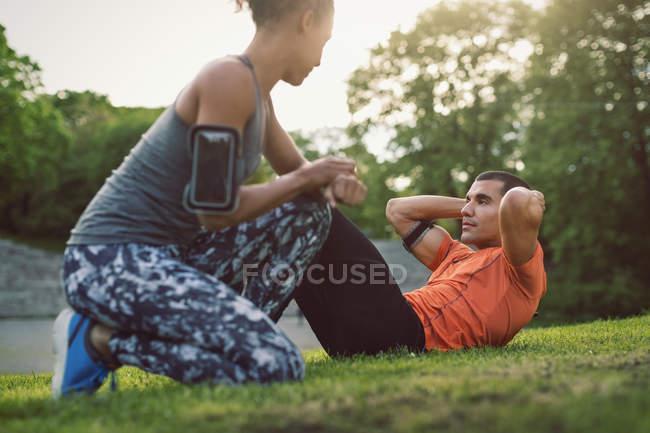 Frau kniend und mit Blick auf Mann Sit im park — Stockfoto