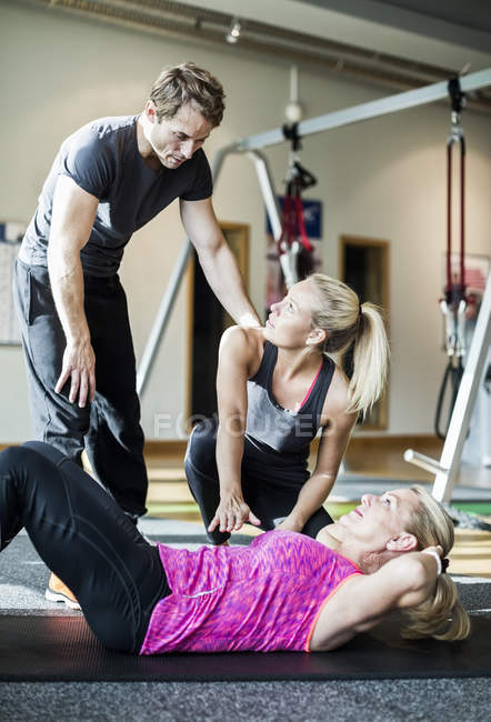 Instructors with senior woman doing sit-ups at health club — Stock Photo
