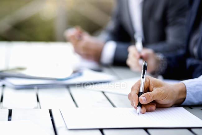 Кадроване зображення бізнесмен написання документа за столом — стокове фото