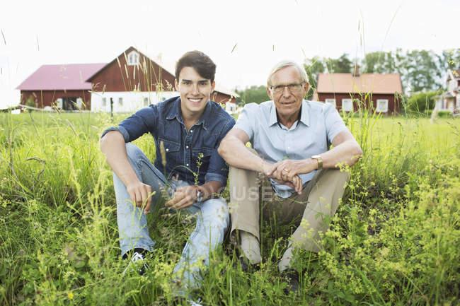 Полная длина портрет дед и внук, сидя на травянистые поля — стоковое фото