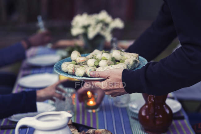 Cropped image of man holding plate with rice paper rolls at outdoor food table during party — Stock Photo