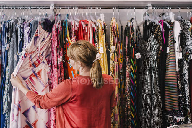 Жінка дивиться на плаття висить на стійці, стоячи в магазині — стокове фото