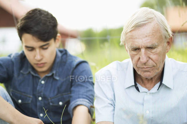 Thoughtful senior man with grandson sitting in yard — Stock Photo