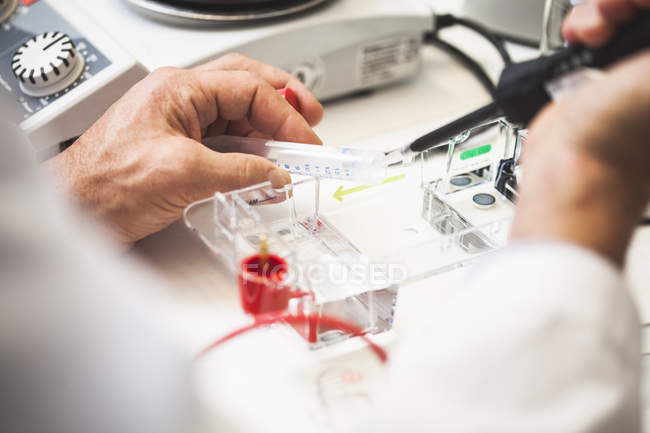 Cropped image of scientist using pipette at laboratory — Stock Photo