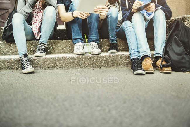 Sección baja de adolescentes que utilizan la tabla digital en los pasos - foto de stock