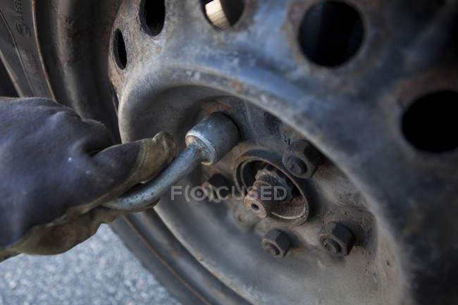 Bild des weiblichen Mechanische Befestigung Autoreifen zugeschnitten — Stockfoto