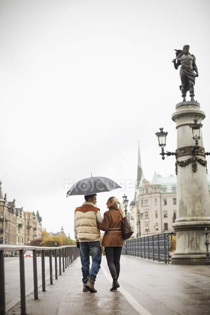 Rear view of young couple with umbrella walking on bridge — Stock Photo