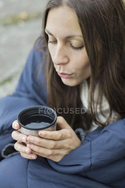 Mulher embrulhado no cobertor, soprando sobre café — Fotografia de Stock