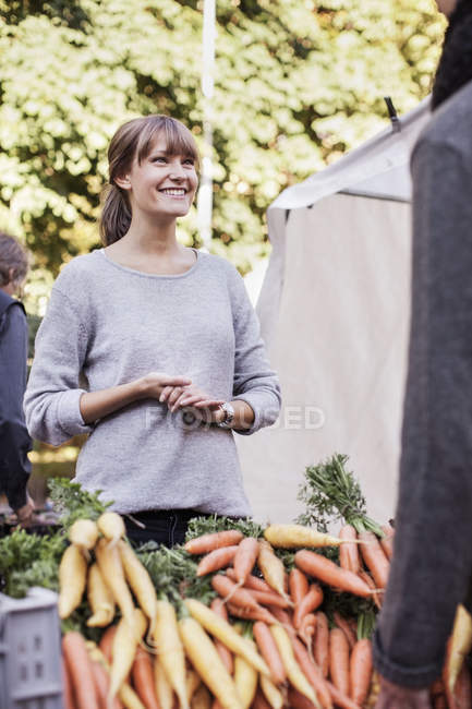 Female vendor selling vegetables at market — Stock Photo