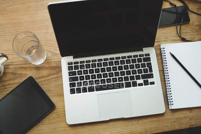 Vista di alto angolo di tecnologie con blocco note sulla tabella — Foto stock