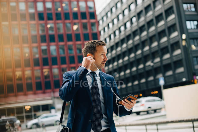 Mature businessman positioning earphones while walking against buildings in city — Stock Photo