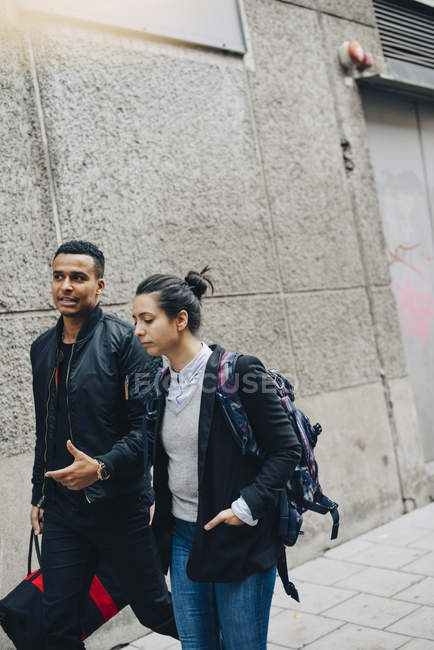 Friends talking while walking on sidewalk by wall in city — Stock Photo