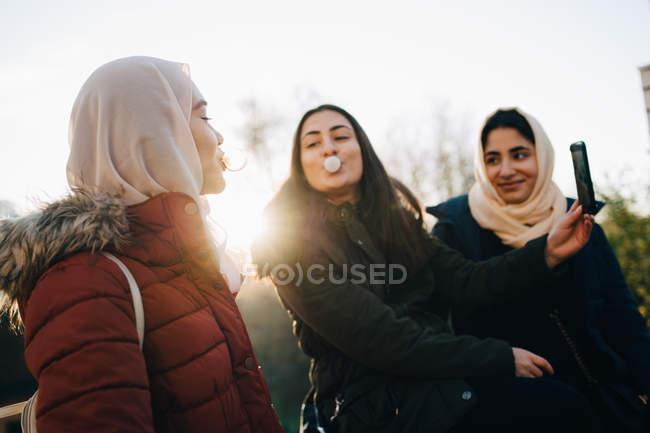 Multi-étnicas amigas soplando encías de burbuja mientras se toman selfie contra el cielo - foto de stock