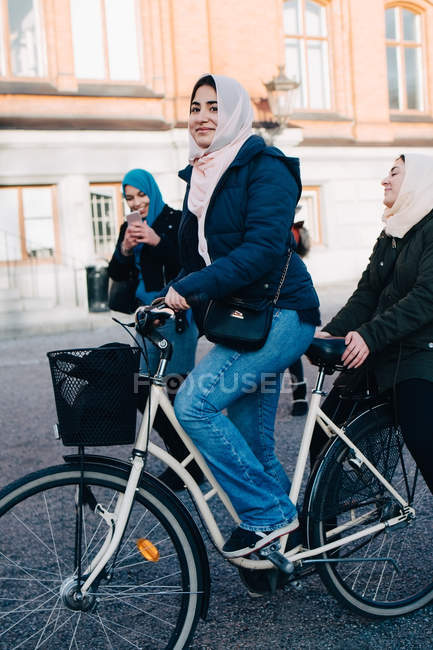 Smiling teenage girl riding bicycle with friend in city — Stock Photo