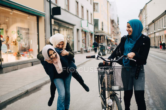 Young woman walking with bicycle looking at cheerful teenage girl giving piggyback to friend on street in city — Stock Photo