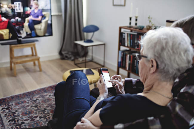 High angle view of senior couple sitting with smart phone watching TV at home — Stock Photo